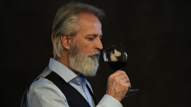 vídeos y material grabado en eventos de stock de sommelier senior degustación de vino tinto - saborear