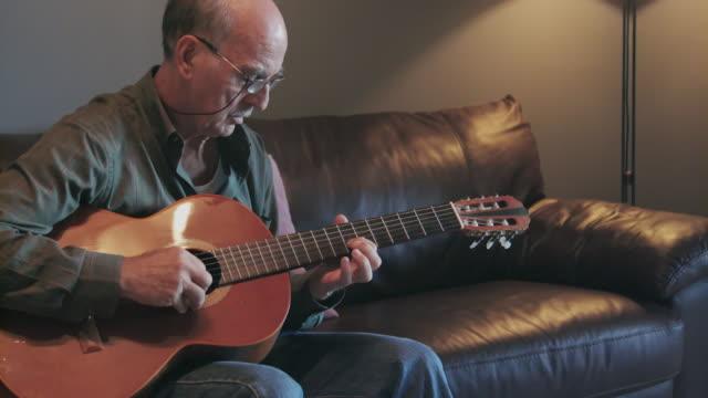 vídeos y material grabado en eventos de stock de senior hombre europeo meridional juegos guitarra - guitarrista