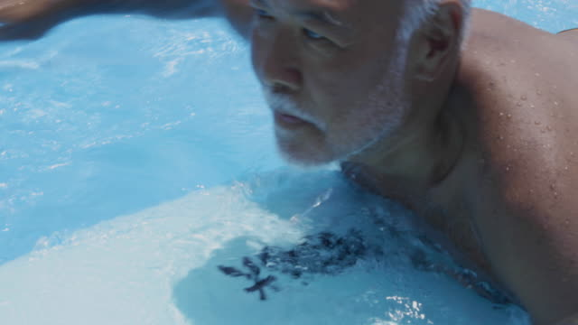 senior surfer is floating on the surfboard in the pool - 挑戦点の映像素材/bロール