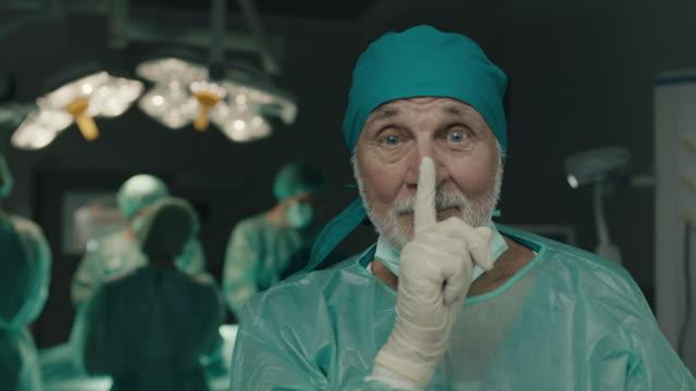 chirurgo anziano che chiede di stare zitto con il dito sulle labbra - silenzio video stock e b–roll