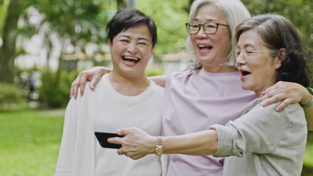 senior taiwanese women looking at smart phone and laughing - wellbeing stock videos & royalty-free footage