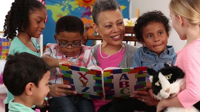 senior teacher reading book to kindergarteners
