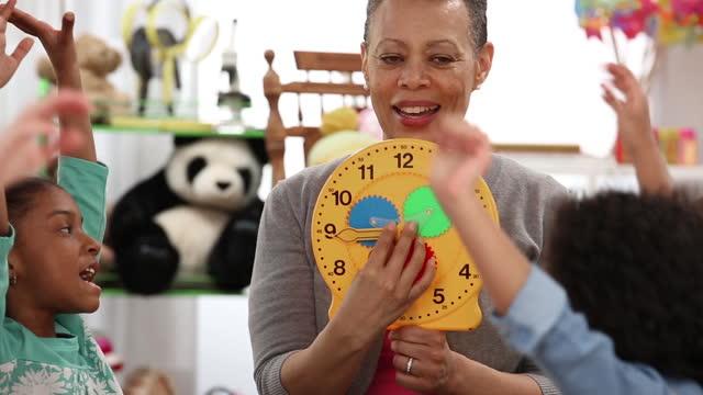 vídeos y material grabado en eventos de stock de senior teacher teaching kindergarteners how to tell time - maestra