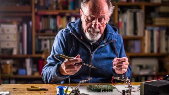 leitender techniker bauteile auf eine platine löten - messgerät stock-videos und b-roll-filmmaterial