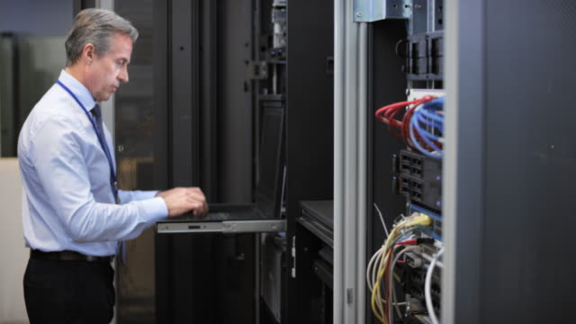 ds senior technician working on a laptop in the server room - technician stock videos & royalty-free footage