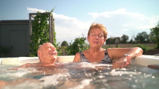 Senior Tenderness, happy smiling senior couple in whirlpool in garden