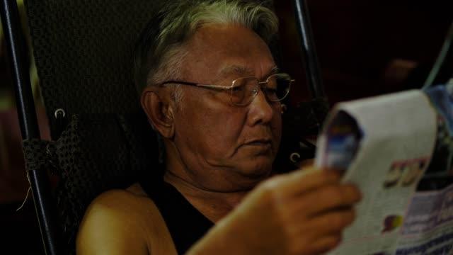 senior thai man reading newspaper - sitting stock videos & royalty-free footage