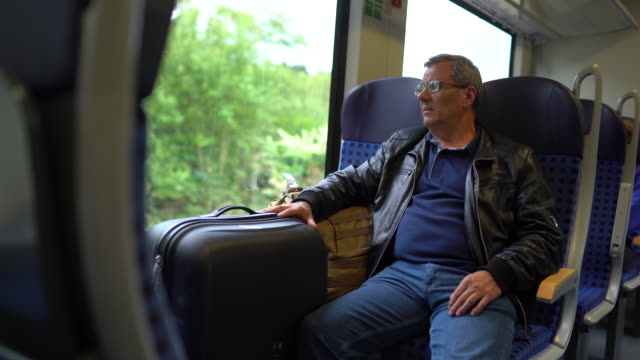 senior tourist traveling in train with his luggage - bag stock videos & royalty-free footage