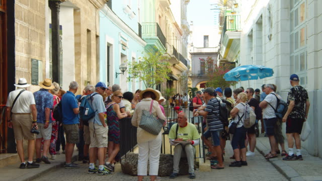 senior tourists gather at a colonial-style quadrangle in old havana, cuba - narrow stock videos & royalty-free footage