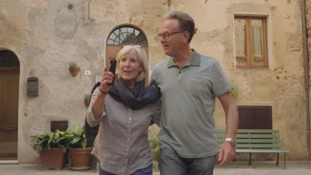 stockvideo's en b-roll-footage met senior tourists taking photo with smart phone - stadsreis