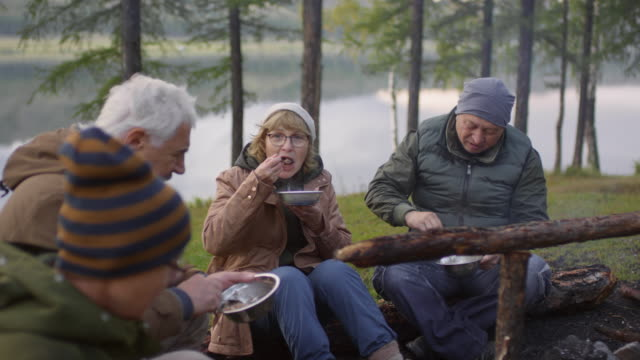 Senior Travelers Eating Camping Meal beside Fireplace