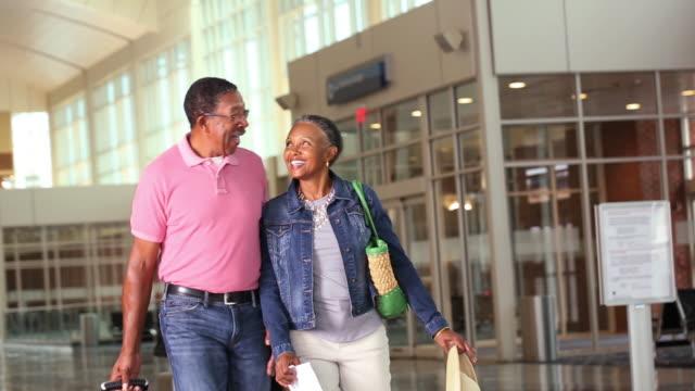 vidéos et rushes de senior travelers in airport - valise
