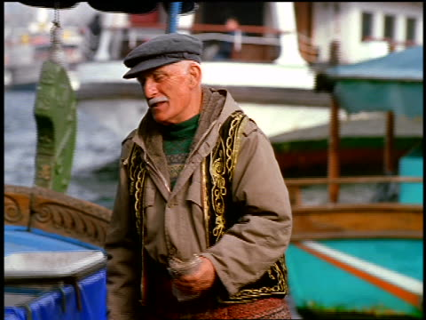 senior turkish man in hat holding money talking to someone on boat offscreen / istanbul, turkey - moustache stock videos & royalty-free footage