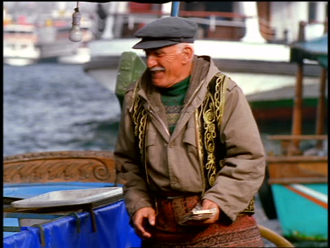 senior turkish man in hat taking food from unseen person on boat + giving it to other man on dock - einzelner senior stock-videos und b-roll-filmmaterial