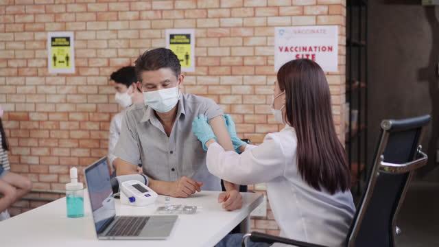 vídeos de stock, filmes e b-roll de idosos recorrem para obter a vacina no local de vacinação covid-19 com distanciamento social, mulher asiática jovem médica prestes a aplicar dose no braço do idoso asiático usando uma máscara facial protetora. um velho sorrindo para dose imunológic - 20 29 years