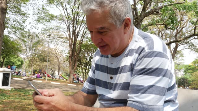senior using smartphone in the park - good news stock videos & royalty-free footage