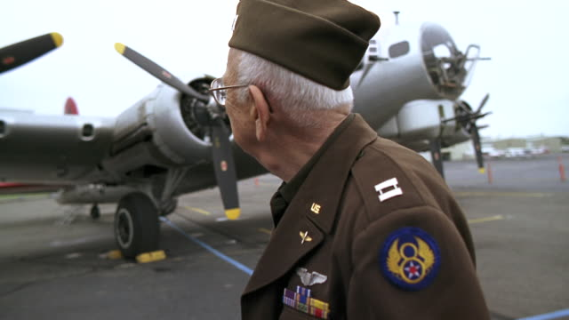 vidéos et rushes de ms senior veteran in military uniform looking back at b-17 flying fortress propeller airplane and smiling / seattle, washington, usa - tourner