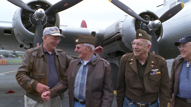 ms senior veterans in military uniforms walking near b-17 flying fortress propeller airplane and shaking hands / seattle, washington, usa - veteran stock-videos und b-roll-filmmaterial