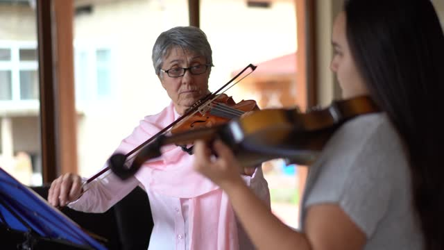 女の子にバイオリンを弾く教師を教える上級バイオリン教師 - バイオリン奏者点の映像素材/bロール