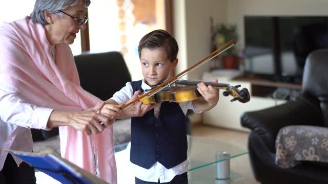 ヴァイオリンを弾く小さな男の子を教える上級バイオリン教師 - 再開点の映像素材/bロール