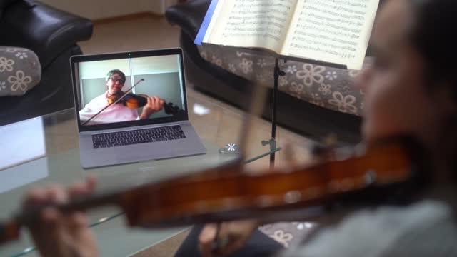 senior violin teacher teaching online a girl how to play violin - violin stock videos & royalty-free footage