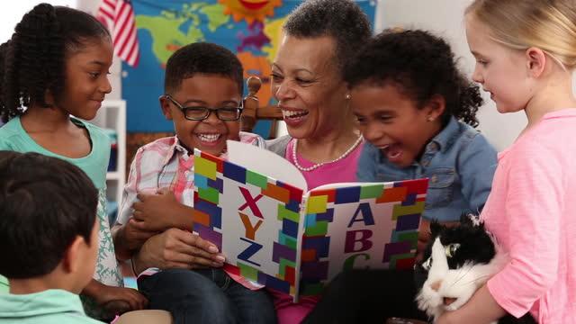 senior volunteer reading book to kindergarteners
