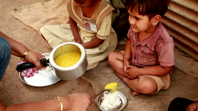 senior volunteer woman serving food to rural children - hungry stock videos and b-roll footage