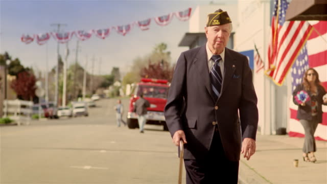 senior war veteran walking down street after parade / california - veteran stock-videos und b-roll-filmmaterial