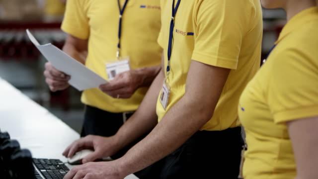 vídeos y material grabado en eventos de stock de empleado de almacén mayor supervisión de jóvenes compañeros de trabajo introducción de datos en la computadora en el almacén - parte de una serie