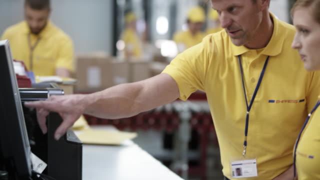 vidéos et rushes de magasinier principal enseignement un collègue féminin comment entrer des données dans le document d'expédition dans l'ordinateur - service postal