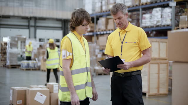 DS Senior warehouse supervisor discussing something with a young trainee