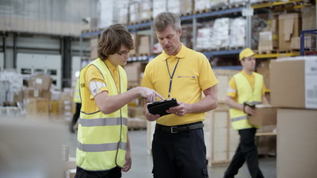 ds senior warehouse supervisor explaining something to a young packer - postal worker stock videos and b-roll footage