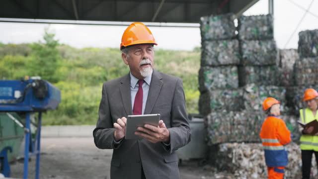 オンサイトでノートを作成するシニア廃棄物管理の専門家 - リサイクル素材点の映像素材/bロール