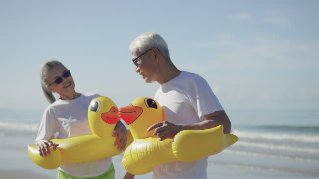 senior wife feeling happiness, smiling, hugging her senior husband for thank you to having a summer vacation together, a mature couple in a couple of cloth, a white t-shirt, green shorts at the beach with a yellow swimming ring. - swimming shorts stock videos & royalty-free footage