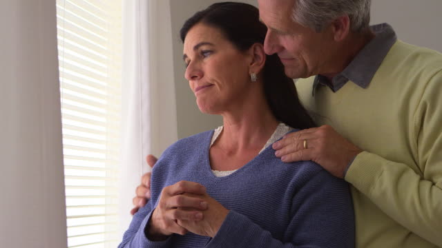 Senior wife grieving by window with husband