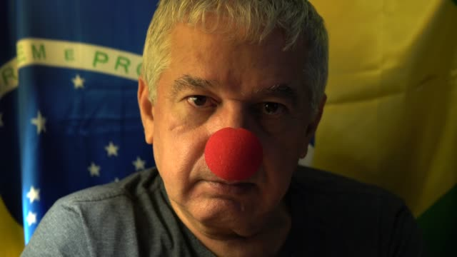 vídeos de stock e filmes b-roll de senior with clown face with reference to brazilian corruption - artista