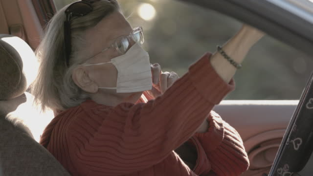 senior with hand sanitizer and mask in car covid-19 protection - cleaning stock videos & royalty-free footage
