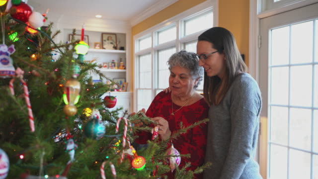 senior woman, a mother, and her daughter decorating a christmas tree together in a living room. - decorating the christmas tree stock videos & royalty-free footage