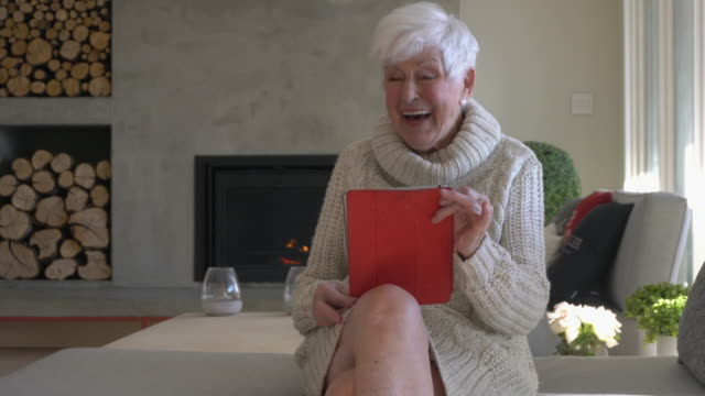senior woman alone using tablet in living room - gazebo stock videos & royalty-free footage