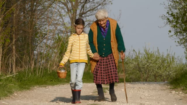 senior woman and child walking down the road. holding hands. - affectionate stock videos & royalty-free footage