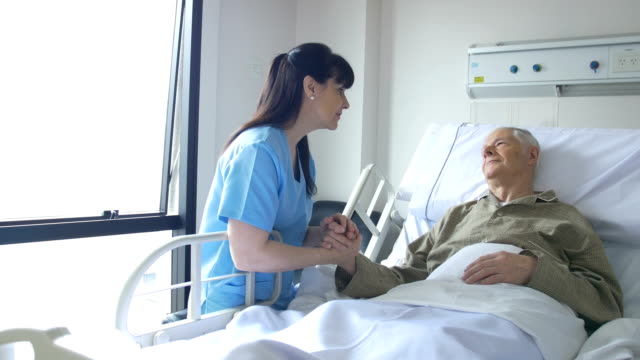 Senior woman and female nurse communicating in hospital