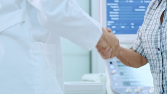 Senior woman and her doctor shaking hands in the office