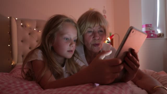 senior woman and her granddaughter using a digital tablet - duvet stock videos & royalty-free footage