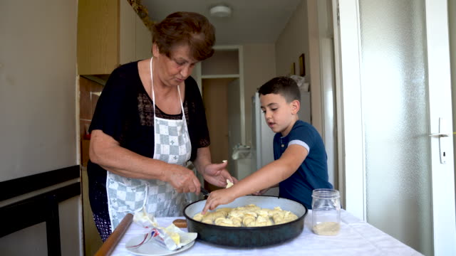 senior woman and her grandson preparing dinner together - french food stock videos & royalty-free footage
