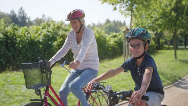 ts senior woman and her grandson riding their bikes in the sunny park - sports helmet stock videos & royalty-free footage