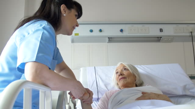 senior woman and nurse communicating in hospital - female nurse stock videos and b-roll footage