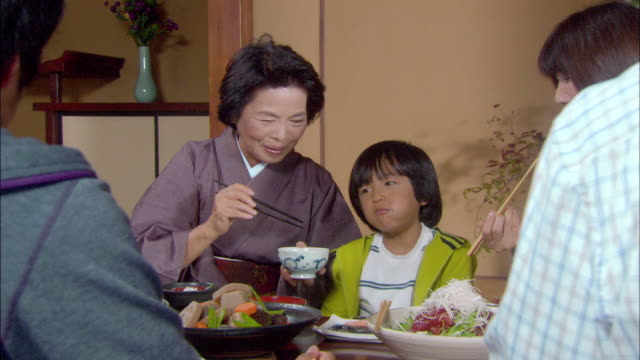 ms zoom out senior woman and young boy eating/ tokyo, japan - eating utensil stock videos and b-roll footage