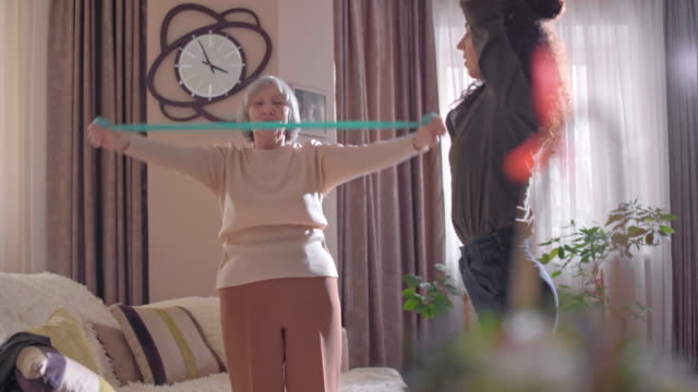 Senior woman and young volunteer exercising at home