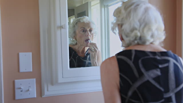 MS Senior woman applying lipstick in bathroom mirror / Portland, Oregon, USA