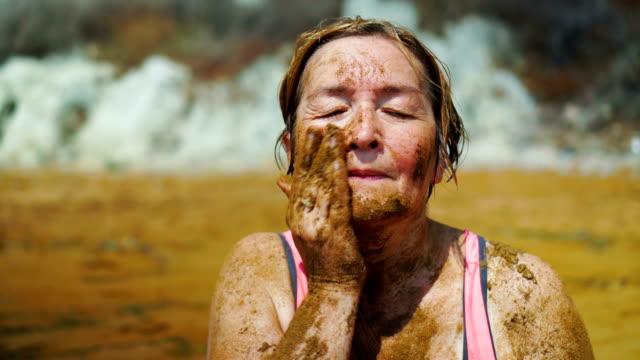 Ältere Frau Schlamm im Gesicht anwenden.